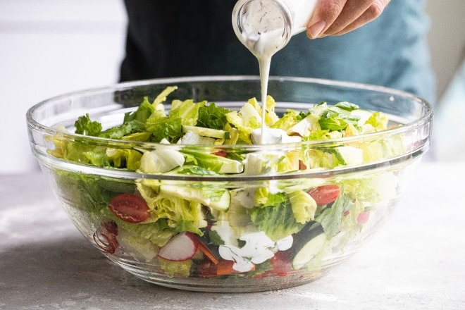 Ranch dressing being poured onto an easy garden salad in a clear bowl.