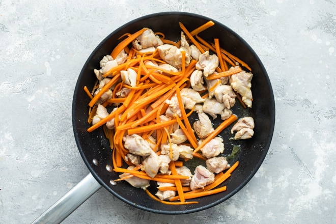 Chunks of chicken and sliced carrots sauteing in a black skillet.