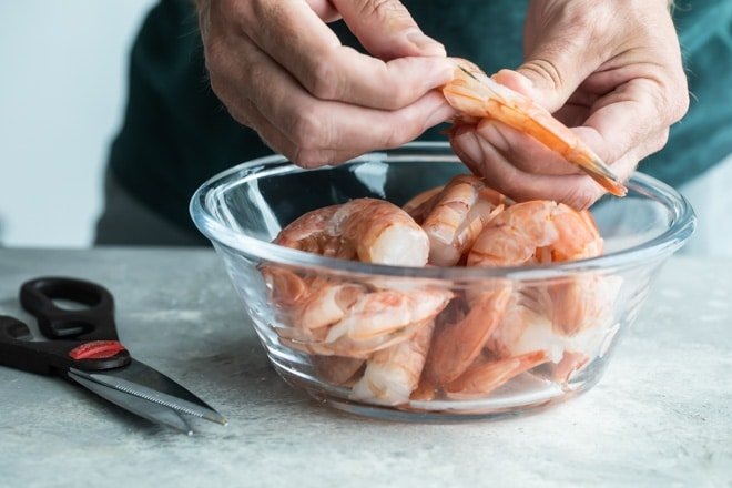 Someone taking the tails off of raw shrimp with some in a clear bowl.