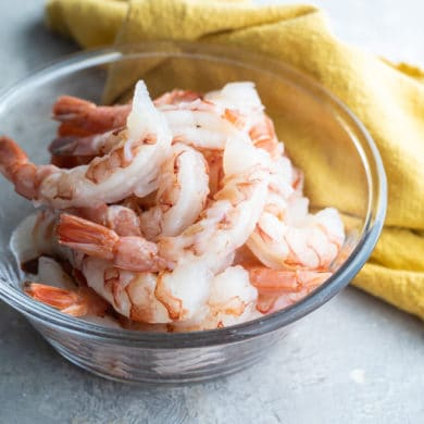 Raw shrimp in a clear bowl.
