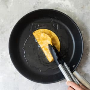 Someone flipping a corn tortilla in a black skillet with tongs.