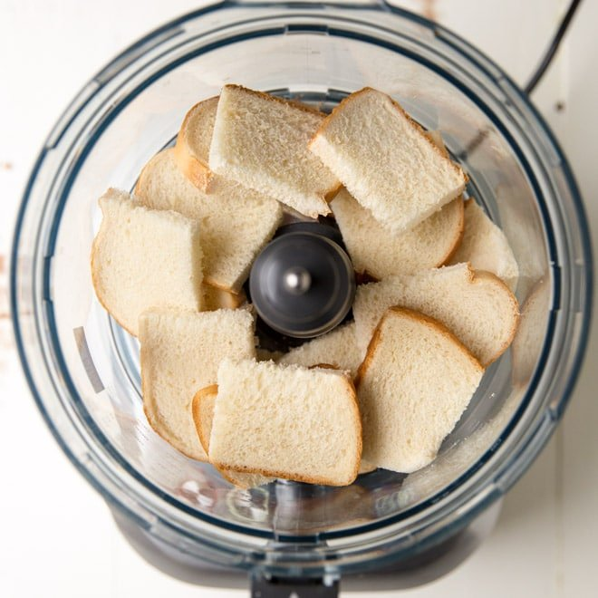 Chunks of white bread in a food processor.