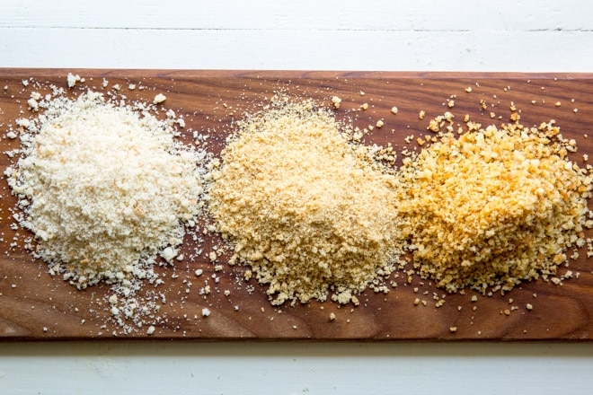 Three different types of breadcrumbs in piles on a wooden cutting board.