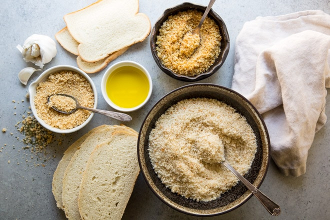 Different types of bread crumbs in various bowls surrounded by slices of bread.