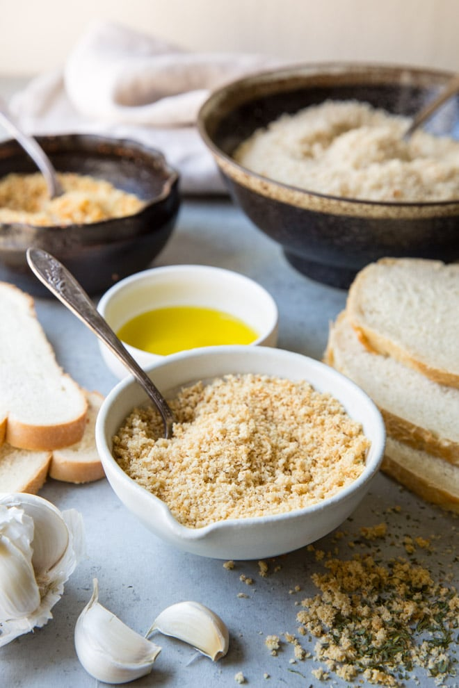 Homemade breadcrumbs in a white bowl with a spoon.