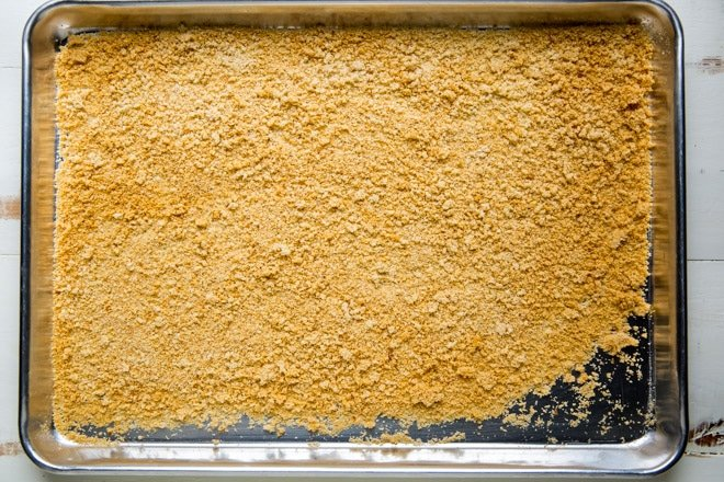 Breadcrumbs on a sliver baking sheet.