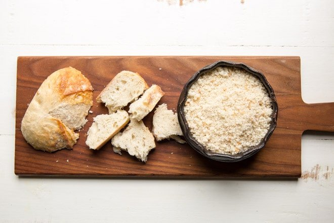 French bread, chunks of french bread, and a bowl of french breadcrumbs on a wood cutting board.