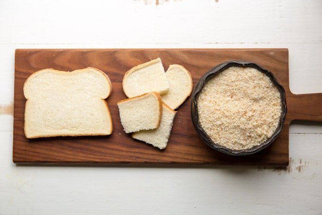 A slice of white bread, chunks of white bread, and a bowl of white breadcrumbs on a wood cutting board.