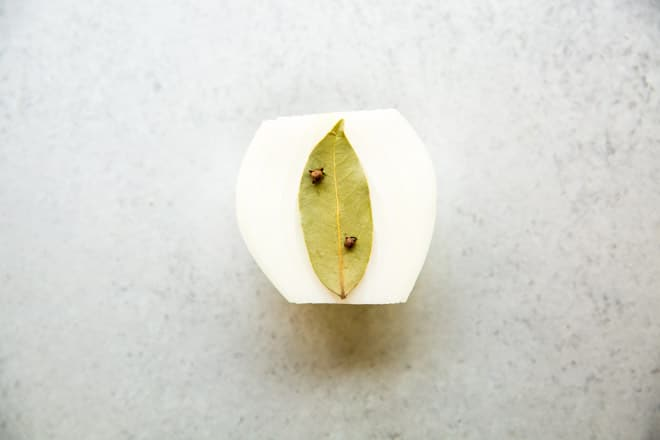 Half of an onion with a bay leaf attached to it with whole cloves.