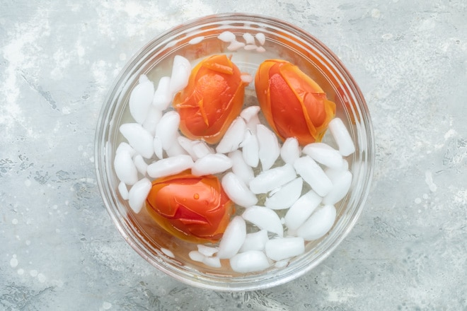 Three tomatoes being blanched in iced water in a clear bowl.