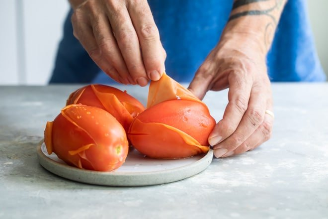 Someone peeling three tomatoes on a white plate.