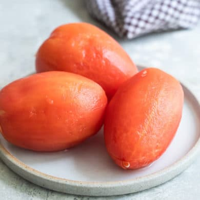 Three peeled tomatoes on a white plate.