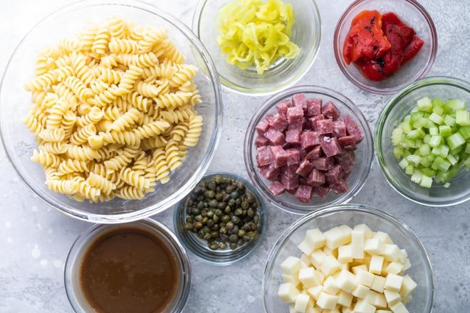 Italian pasta salad ingredients in various bowls.