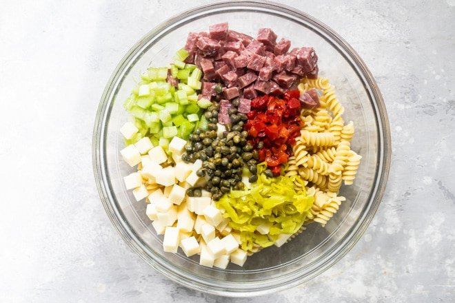 Separated Italian pasta salad ingredients in a clear bowl.