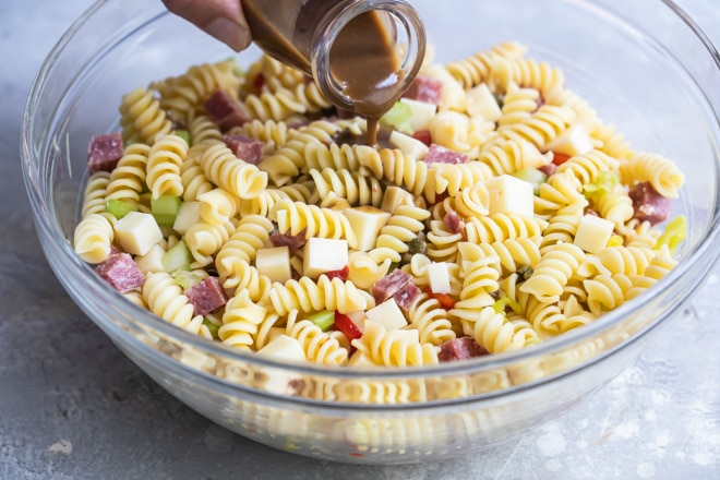 Dressing being poured onto Italian pasta salad in a clear bowl.