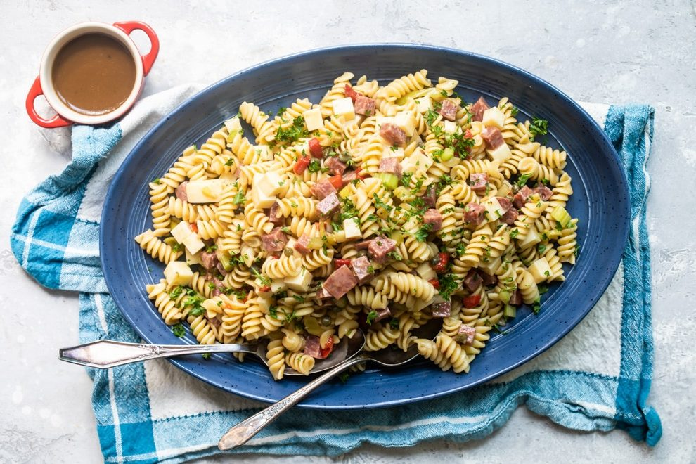 Italian pasta salad on a blue platter with a serving spoon and fork.