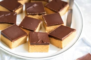 No bake peanut butter bars on a white platter with a knife.