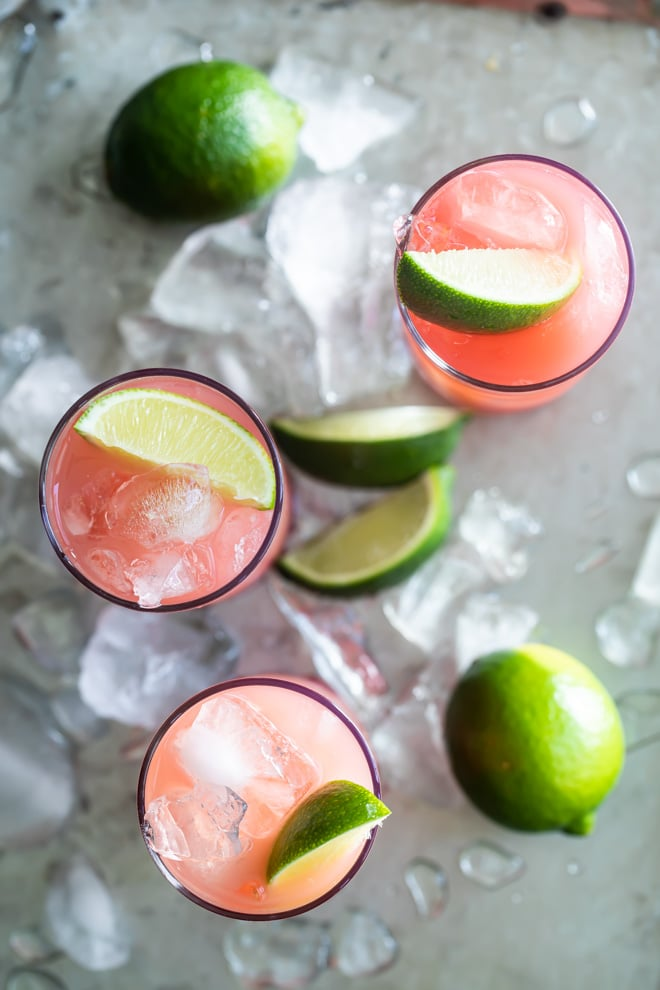 Seabreeze cocktail in three glasses on a silver serving tray with ice and sliced and whole limes.