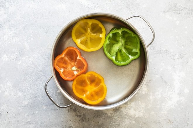 Four peppers with the tops cut off and cored in water in a sliver pot.