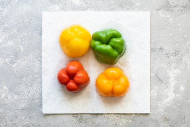 Four bell peppers on a white paper towel.