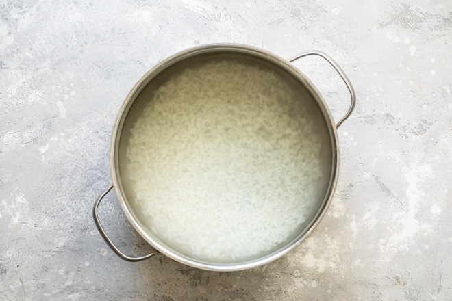 Rice cooking in a sliver pot.