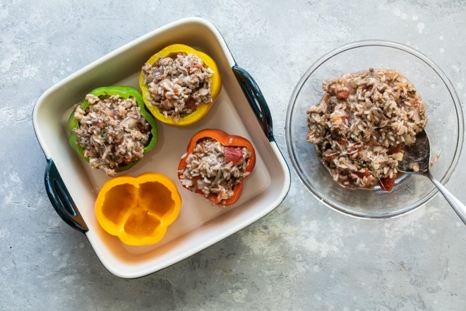 Stuffing for the bell peppers in a clear bowl with 4 peppers in a square baking pan.