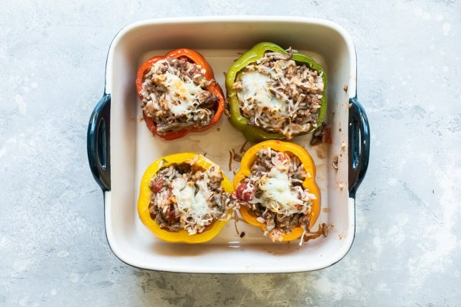 Four stuffed bell peppers in a square baking dish.