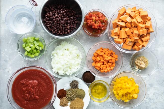 Vegan chili ingredients in various bowls.