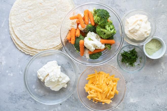 Veggie tortilla roll up ingredients in various bowls.