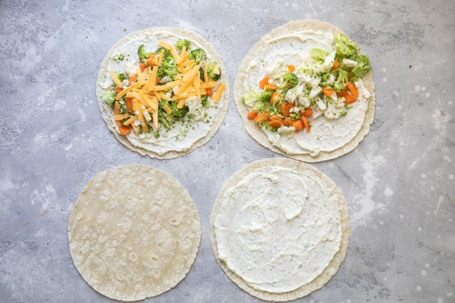Four stages of assembling veggie tortilla roll ups.
