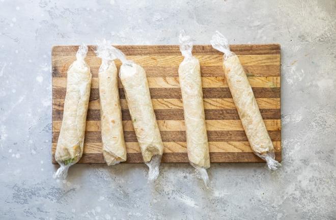 Five veggie tortilla roll ups wrapped in saran on a wood cutting board.