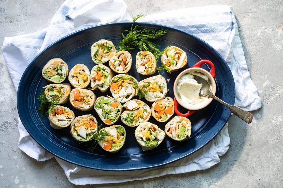 Veggie tortilla roll ups on a blue platter.
