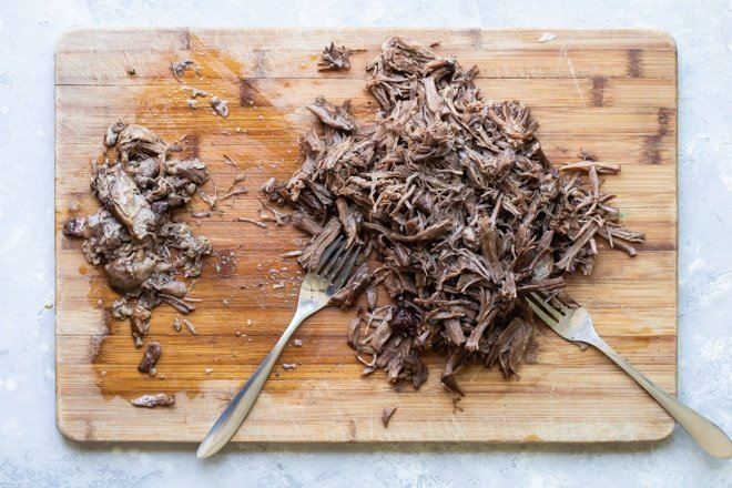 Shredded birria on a wooden cutting board.