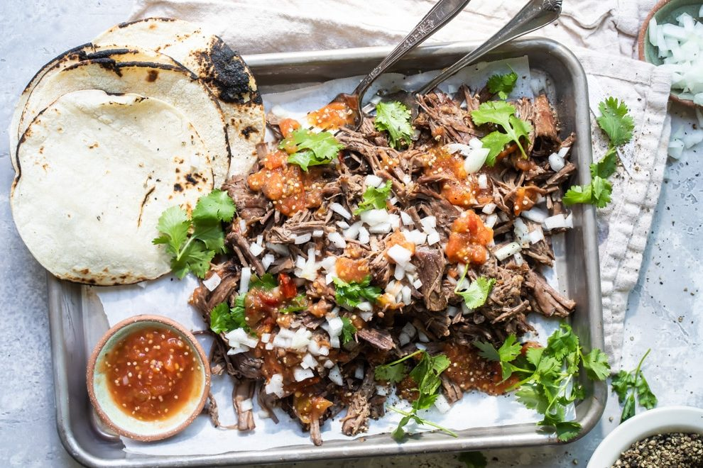 Birria on a silver platter with garnishes.