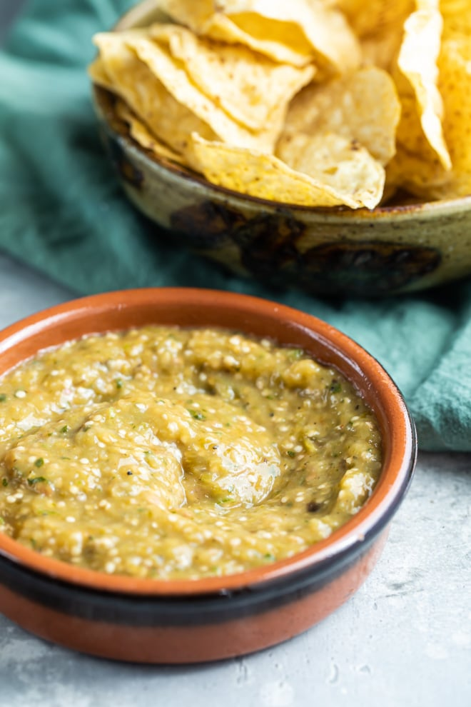 Chipotle tomatillo green chili salsa in a red bowl and a bowl of chips.