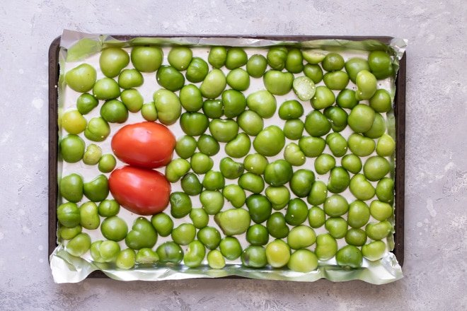A halved tomato and halved green chilies on a baking sheet lined with tin foil.