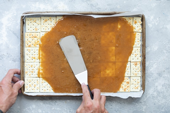 Christmas crack sauce being spread onto the layer of saltine crackers on a baking sheet.