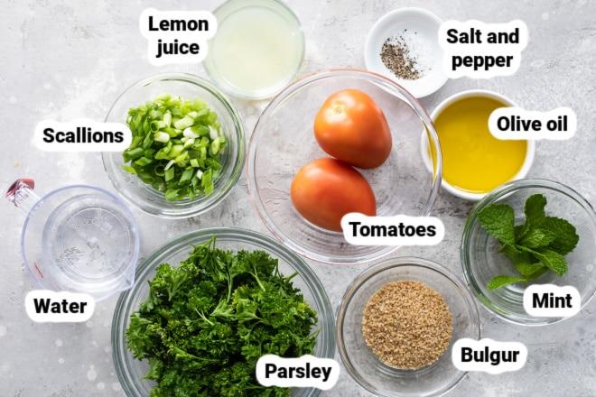 Labeled bulgur tabblouleh ingredients in bowls.