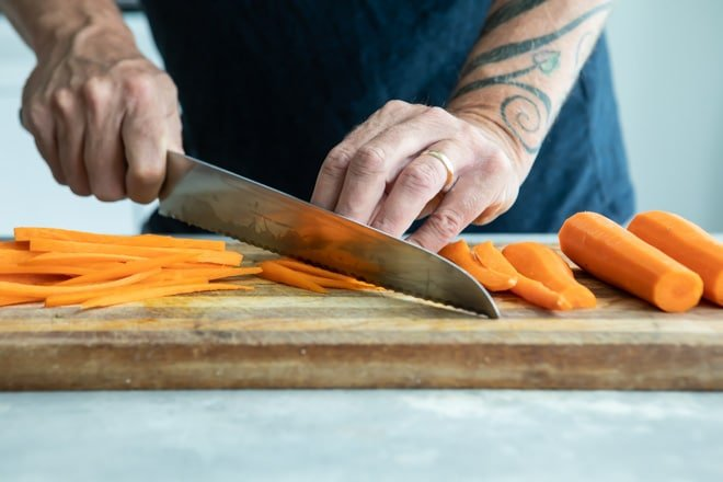 Carrots being julienned on a wooden cutting board.