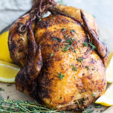 A rotisserie chicken on a white plate with slices of lemon.