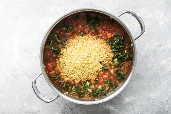 Orzo being added to minestrone soup in a sliver pot.