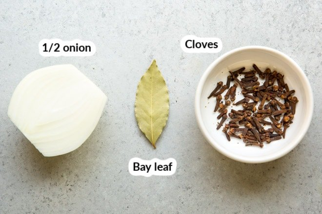 Half of an onion, a bay leaf, and a white bowl of cloves.