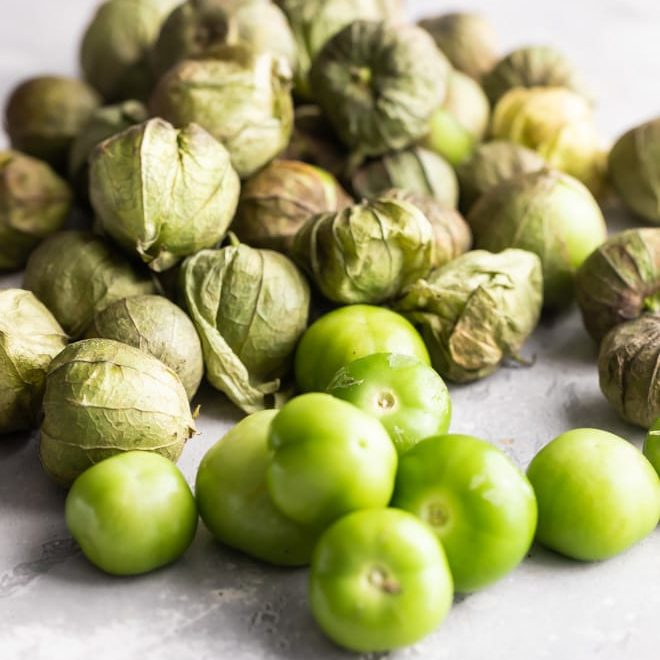 Tomatillos on a gray counter.