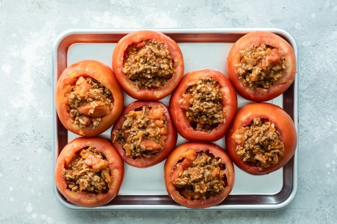 Eight taco stuffed tomatoes on a baking pan.