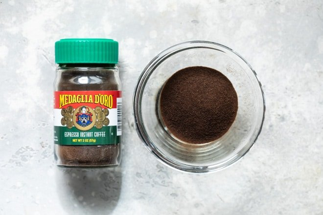 A bottle of instant espresso powder next to a bowl of the same.
