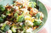 Broccoli salad with bacon and cheese in a green bowl with a spoon.