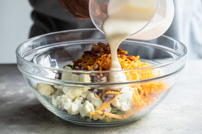 Dressing for broccoli salad with bacon and cheese being poured over the salad in a clear bowl.