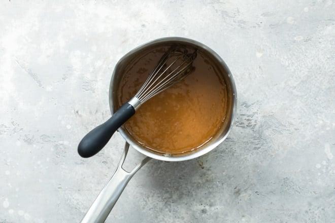 Caramel sauce in a silver sauce pan.