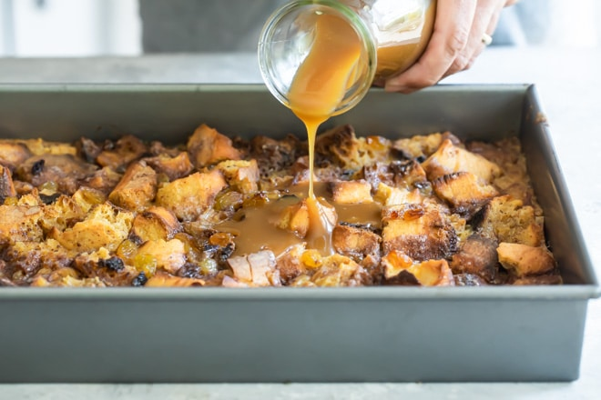 Caramel sauce being poured onto bread pudding.