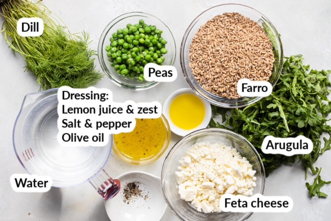 The ingredients for Farro salad in bowls and labeled.